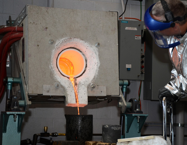 Molten metal is poured from a furnace