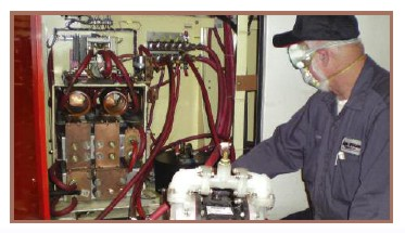 Technician flushes deposits from each power supply cooling path